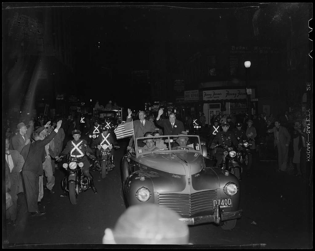 Adlai Stevenson and Paul Dever waving from car moving through parade with police escort