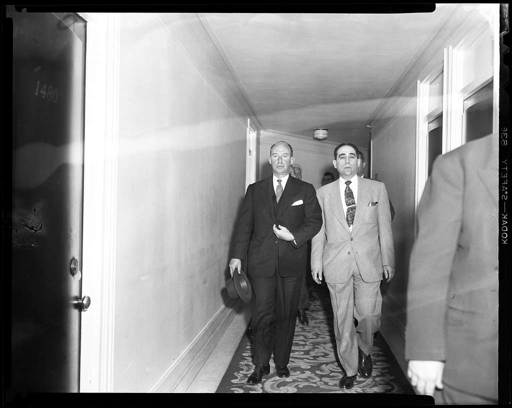Adlai Stevenson and another man walking down a hallway