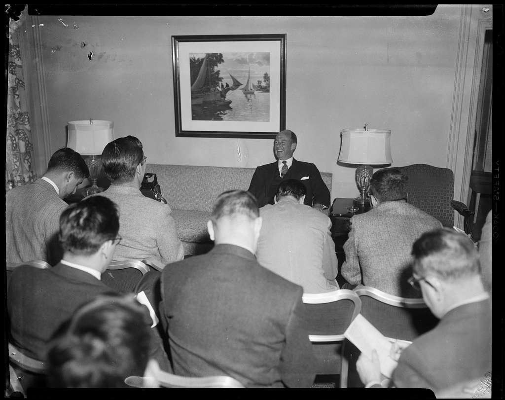 Adlai Stevenson speaking before a group of people in a room