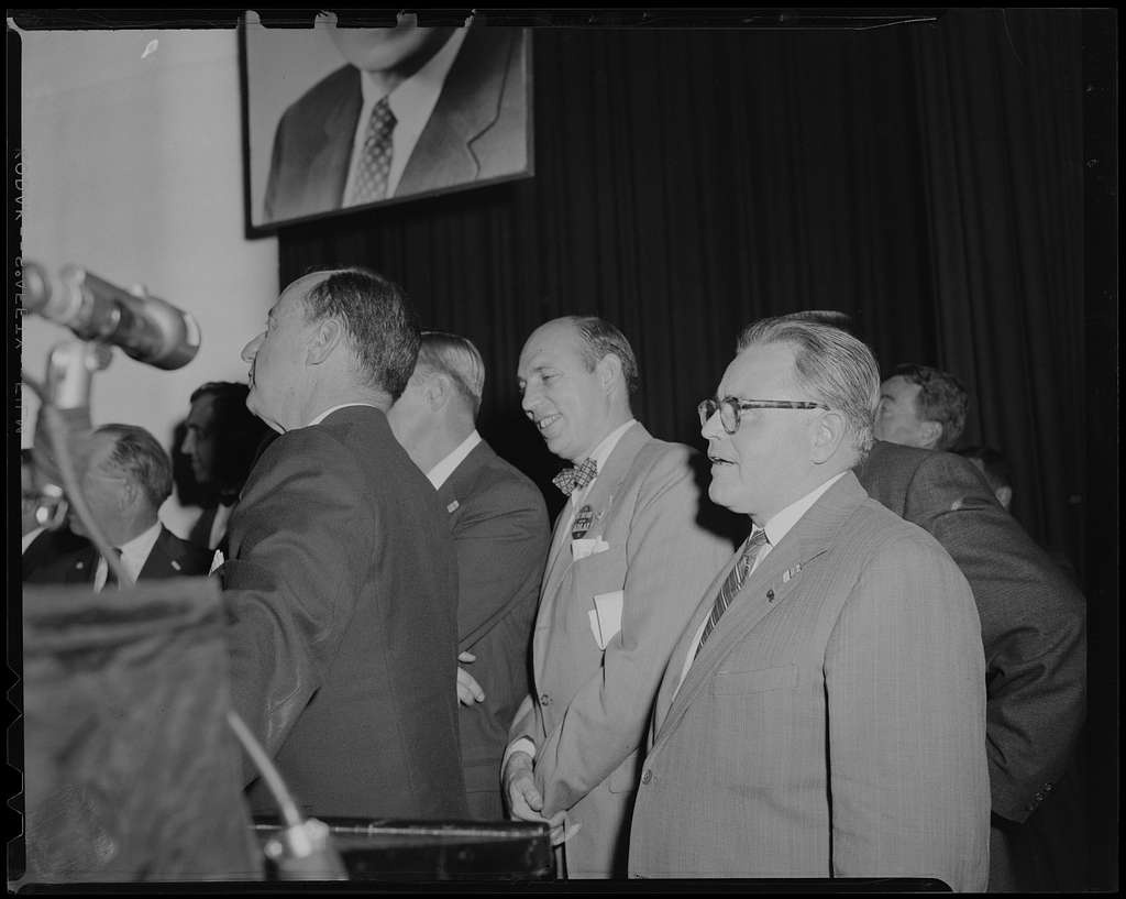 Adlai Stevenson and group of men, looking off camera and seen in profile