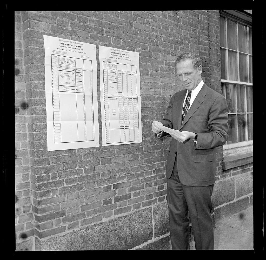 Boston Mayor Kevin White examines Democratic ballot mounted on wall at the Charles Street Meeting House prior to casting his vote